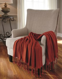 sunset red throw blankets with twisted fringe rested onto a neutral colored accent chair.