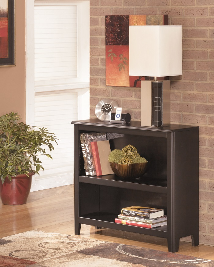 small dark brown bookcase with a lamp on top and books in the shelves