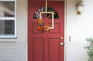 Square fall wreath on the front of a red door.