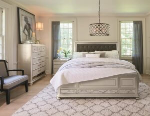 Large bedroom with a white rug and a sparkly chandelier hanging above the bed.