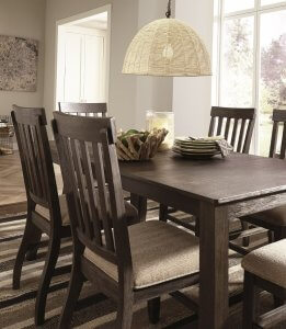 grayish brown table and chairs with cream cushioned seats