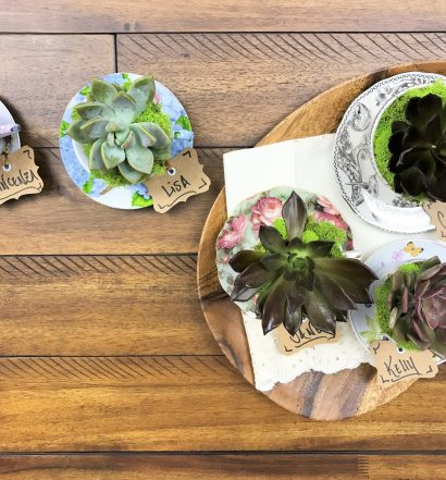 Teacup planters on a wooden tray sitting on a table.