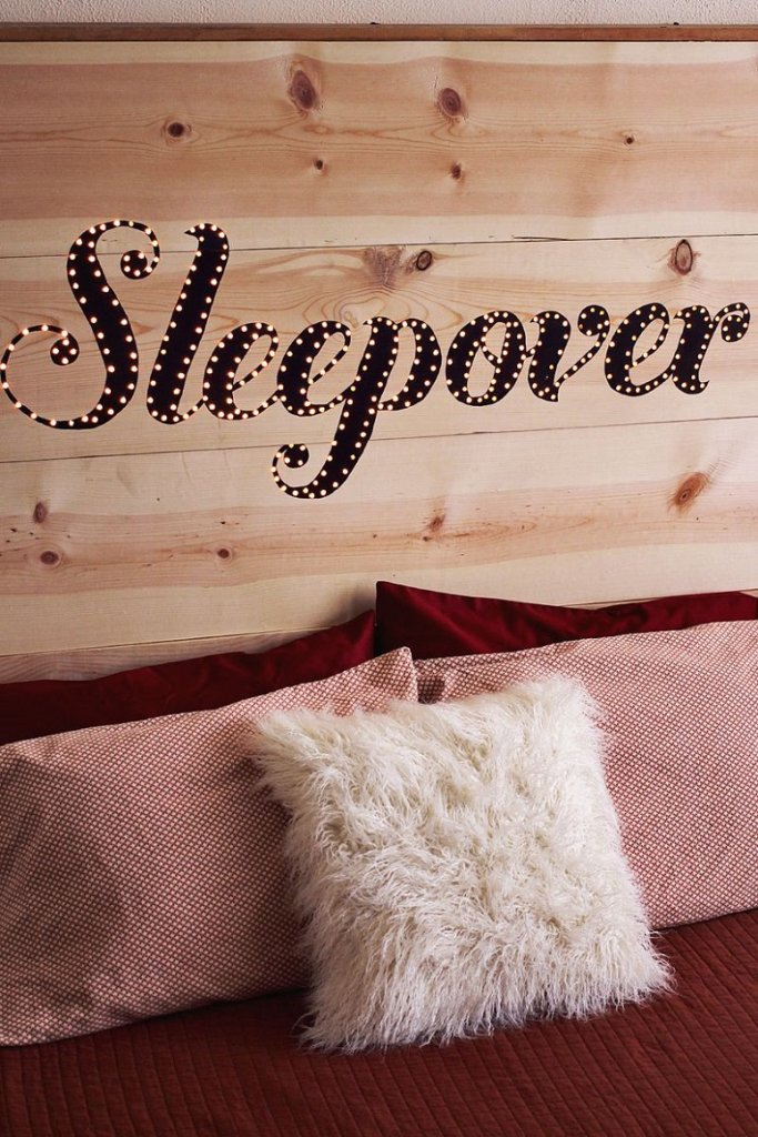 """A wooden headboard with the word """"sleepover"""" on it that lights up."""