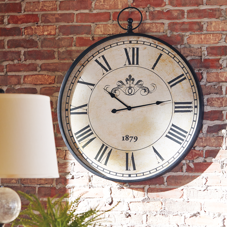 Large wall clock on a brick wall.