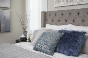 Winter solstice themes bedroom with fluffy pillows and gray and white colors all around.