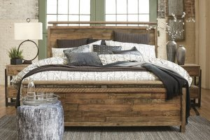 Sommerford brown wood bedroom set with a pouf at the foot of the bed and two nightstands.