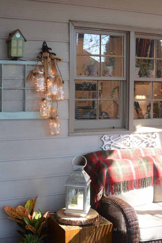 Mason jars with lights inside of them hanging on a shelf on an outdoor patio.