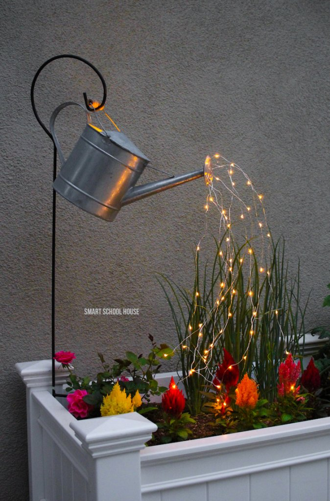 A watering can pouring out lights that flow into a mini garden.
