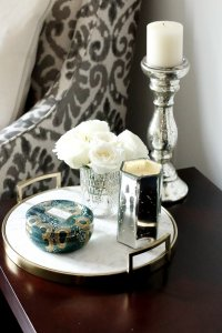 A flat marble tray with a vase of flowers and a candle on top with a accent chair in the background.