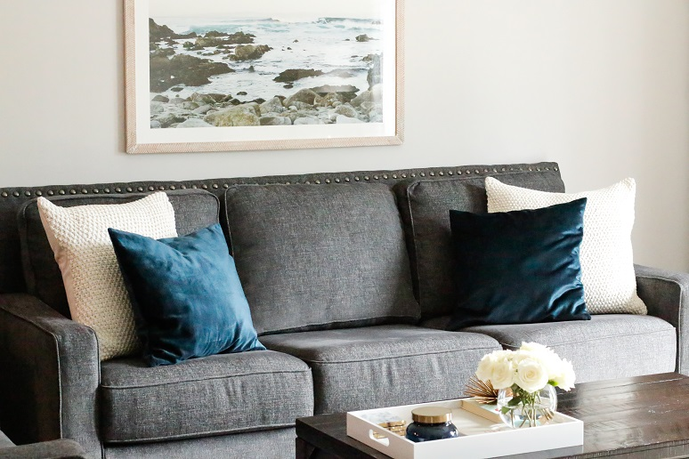 gray sofa with blue velvet pillows decorated on top and a coffee table with a tray on top.