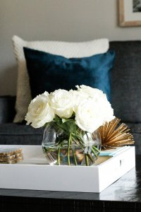 close up shot of a white flat tray with a vase of white flowers inside and blue velvet pillows in the background.