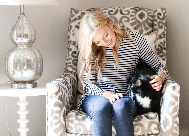 Emily helm sitting on an accent chair with an end table next to her while she is petting her cat
