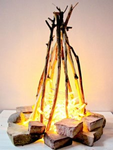 A flameless fire pit made form christmas lights and pieces of wood staged to look like a fire.