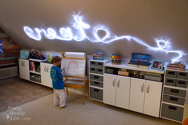"""A kids play room with light up words on the word that say """"Create""""."""