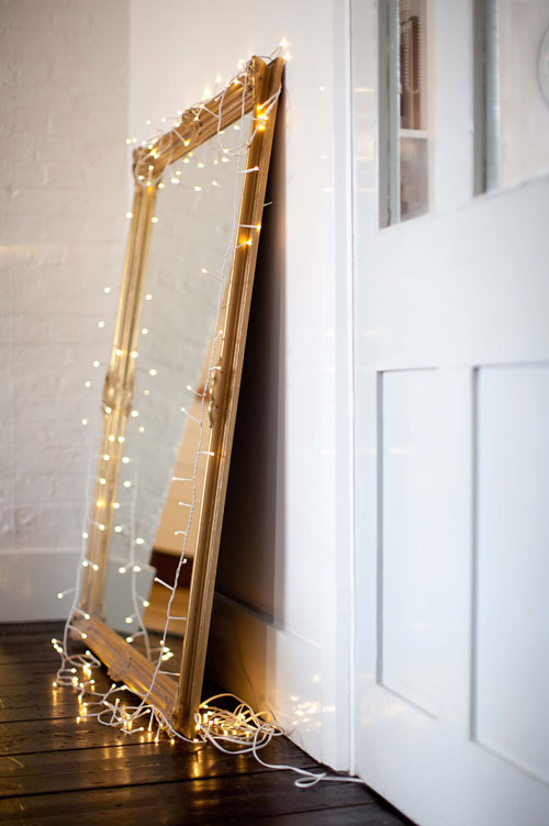 A golden mirror with lights wrapped around it.