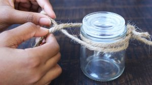 two hands tying hemp string to the top of a small mason jar.