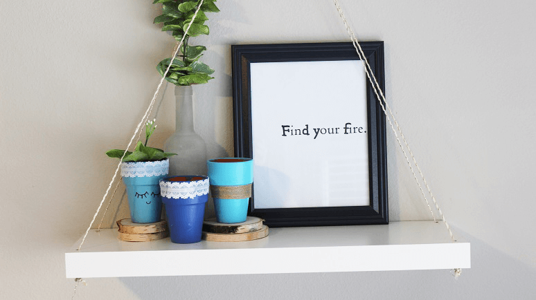 A stencil placed into a frame to display on a wall shelf.