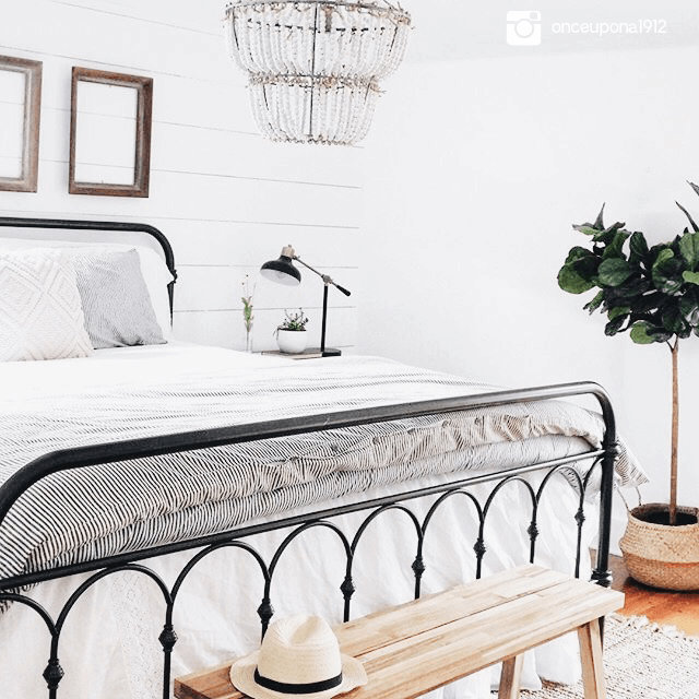 all white and neutral bedroom with a beaded chandelier hanging above the bed.