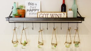 A wall shelf/rack with decor on top such as wine bottles and canvases with plants hanging off the hooks.