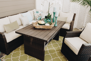 A beautiful covered patio with a neutral colored outdoor sectional decorated with sea foam greens and blues.
