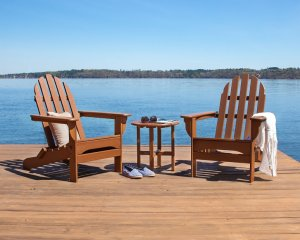 Two brown polywood Adirondack chairs on a dock over looking the ocean.