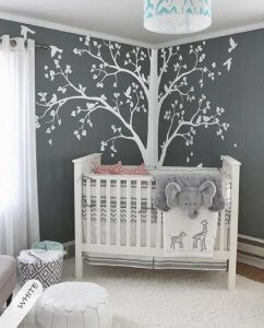 Nursery with a tree decal behind the crib.