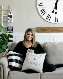 An photograph of jenny caspers on her ashley furniture sofa with a pillow and farmhouse decor surrounding her.