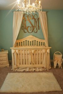 Nursery with drapes over the crib and a chandelier with a monogram also above the crib.