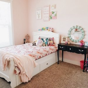 Little girls room with wall decor above the bed.
