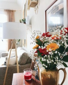 image of spring flowers on a table with a lamp and red candle next to it.