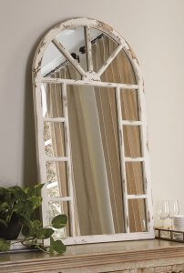A rustic styled wall mirror leaning against a wall on a console table.