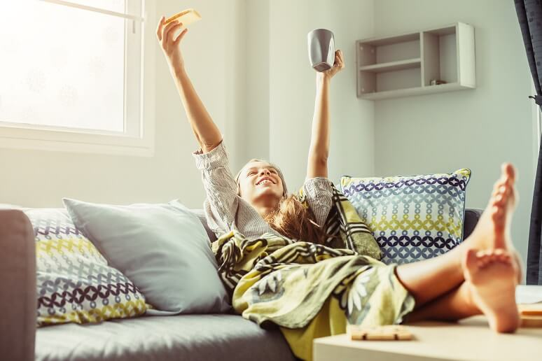 Girl in blanket relaxing on couch in living room