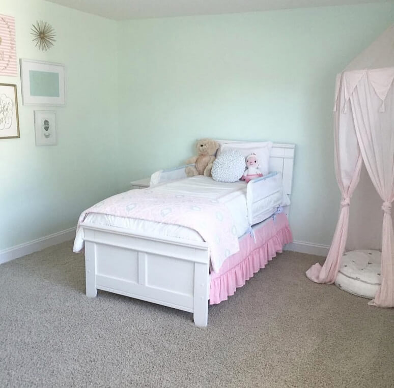 Image of the little girls room before the makeover. There is a white bed with a blank blue wall with a few frames on the wall.