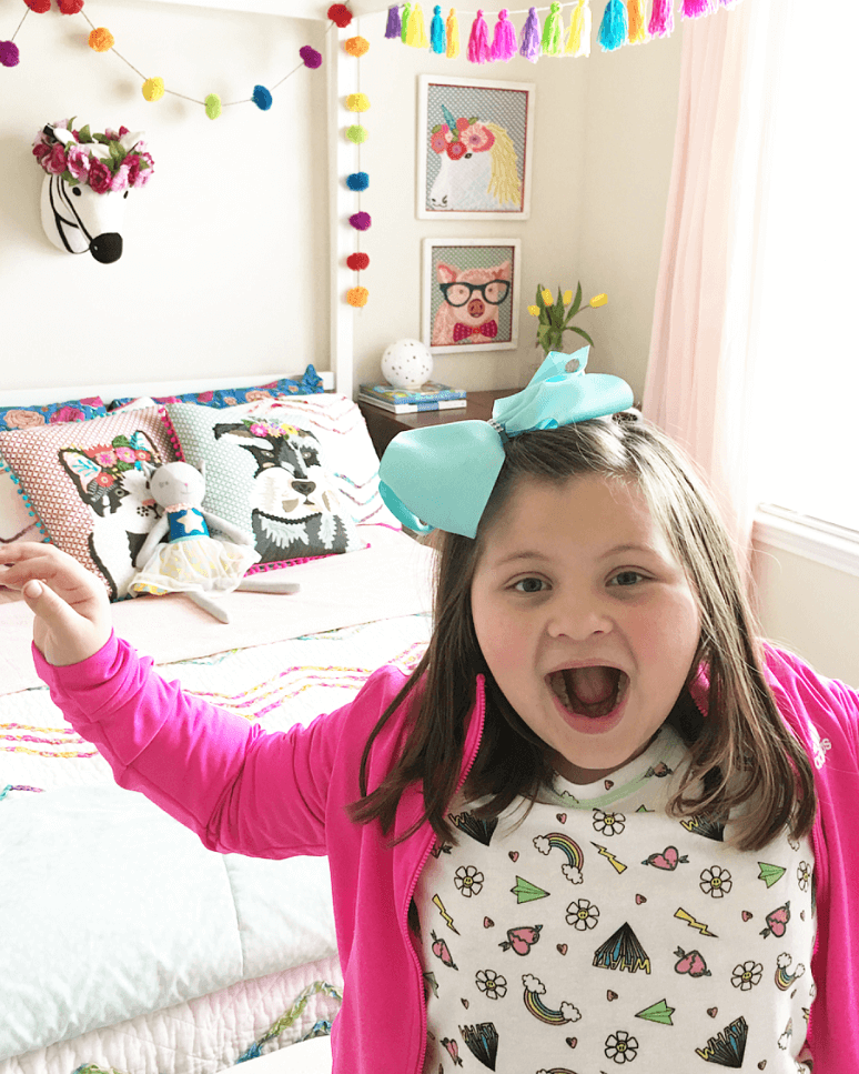 Image of a little girl with a happy excited face while standing in front of a canopy bed.