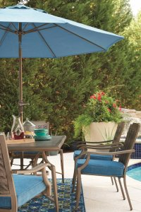 An outdoor dining table on a porch with a blue umbrella hovering above the table.