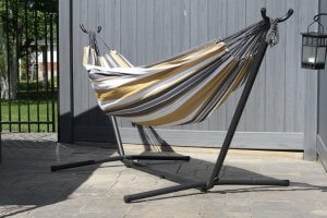 Stripped hammock on a back patio connected to a hammock stand.
