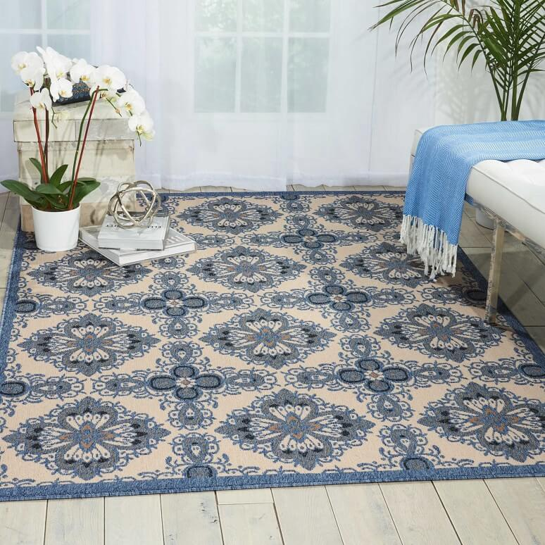 Vintage and blue patterned outdoor rug in a sun room with a planter on the side and a bench on the opposite side.