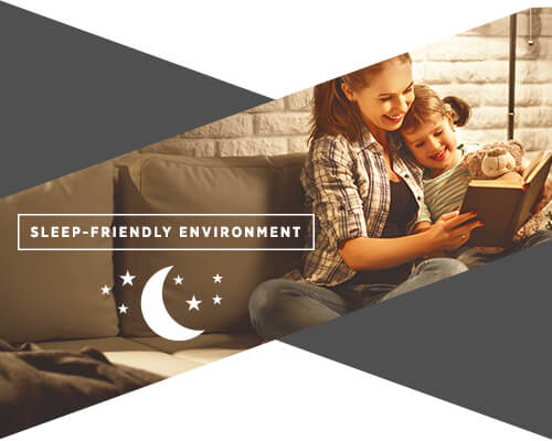 "A graphic of a woman and her daughter on a couch reading a book before bed and the text underneath them reads ""sleep-friendly environment"""
