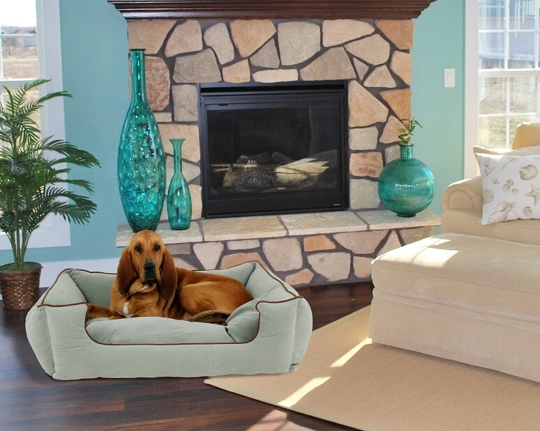 A dog on a dog bed in a living room in front of a fire place with two vases on the side.
