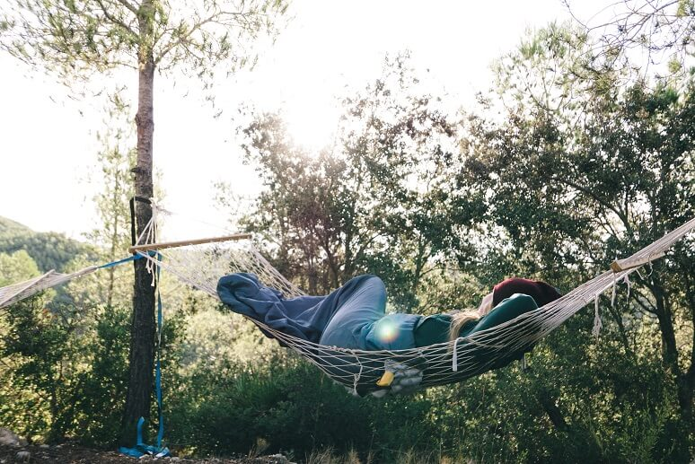 Photograph of a woman in her hammock in the wilderness sleeping under the sun and trees.
