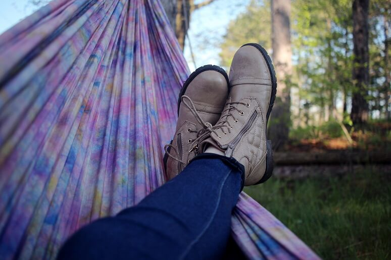 Photograph of a person in a hammock relaxing with their legs crossed while overlooking the wilderness.