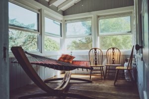 Photograph of a hammock in a sun room with large windows over looking the forest.