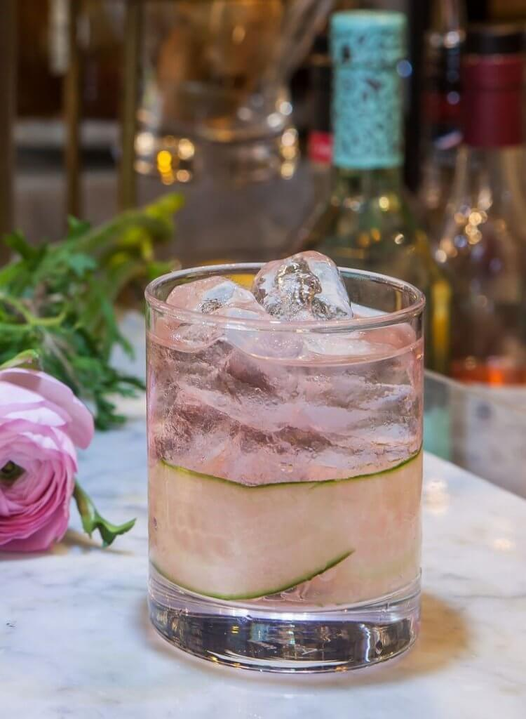 Image of a cocktail in a small short glass with a blush color to is and ice at the top of the drink.