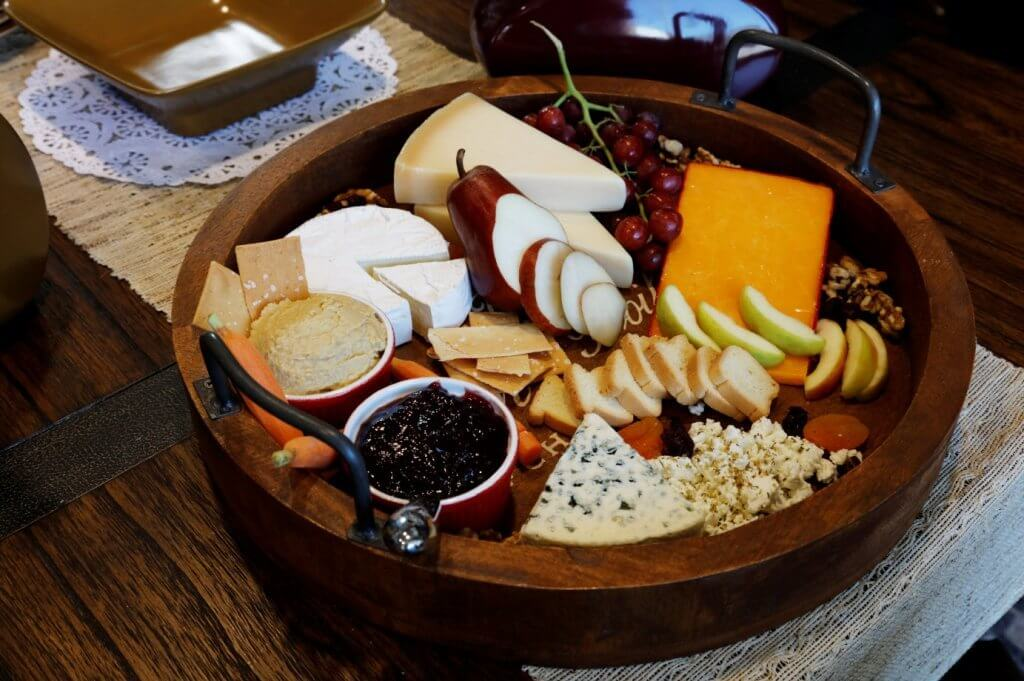 Home Accents Tray, a circular wooden platter made of Mango Wood, displayed with assorted cheeses and crackers.