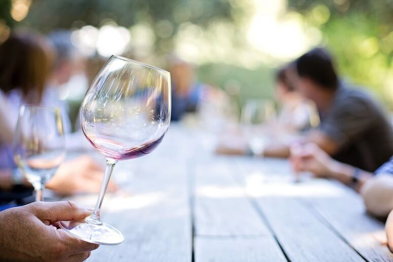 Wine glass on a picnic table with people at a wine party.