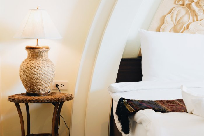 wicker lamp on table next to white bed