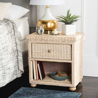 beige wicker nightstand with lamp and plant on top