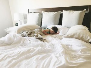 child sleeping in bed with white sheets