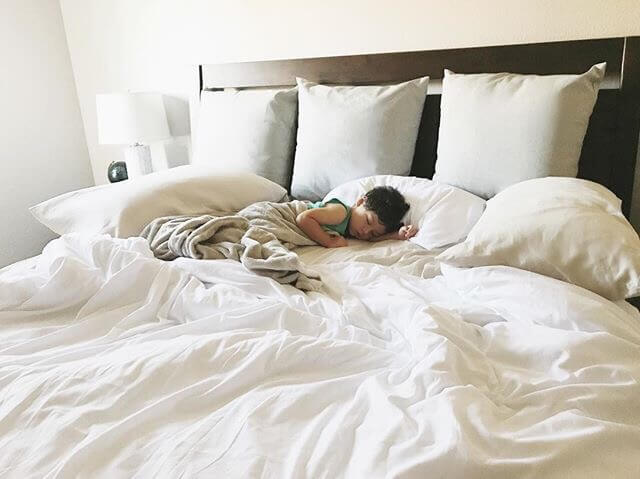 child sleeping on bed with white sheets