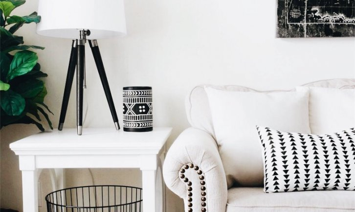 beige couch with white an black pillow next to white nightstand